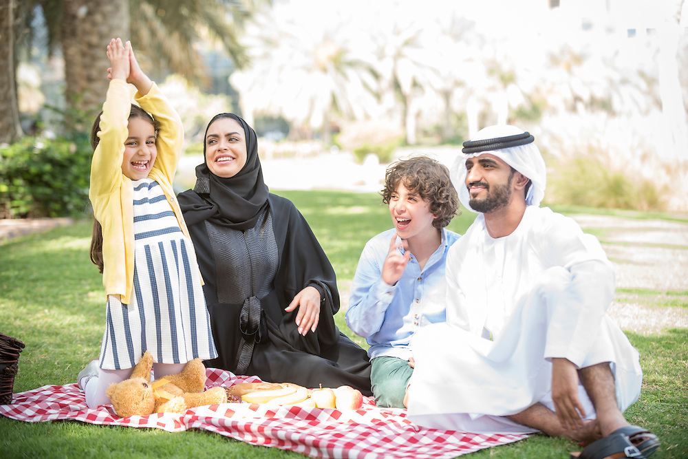 Emirati Arabic family enjoy a picnic outdoors., Mother, father in traditional dressand two children