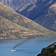 The TSS Earnslaw,  a 1912 Edwardian vintage twin screw steamer on the waters of Lake Wakatipu in, Queenstown, New Zealand. .It is one of the oldest tourist attractions in Central Otago, and the only remaining passenger-carrying coal-fired steamship in the southern hemisphere..The TSS Earnslaw heads along Lake Wakatipu from Queenstown  daily, running tourist trips to Walter Peak Station passing magnificent  peaks and contrasting shoreline foliage along the lakeside. Queenstown, New Zealand. 16th April 2011. Photo Tim Clayton
