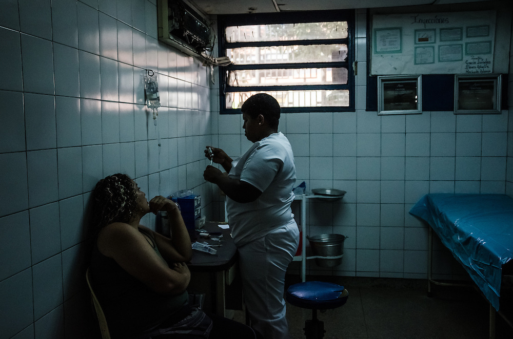 CARACAS, VENEZUELA - JANUARY 21, 2015: A doctor treats a woman brought to the emergency room of the state hospital in the Petare slum in Caracas. Doctors here say they are working with a bare minimum of supplies, and often have to turn patients away. Despite being a petro-state with one of the largest oil reserves in the world, basic and advanced medical supplies from gauze and surgical gloves, to heart stints, are difficult to find in hospitals and pharmacies across Venezuela.