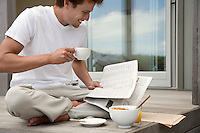 Man having breakfast and reading papers on porch