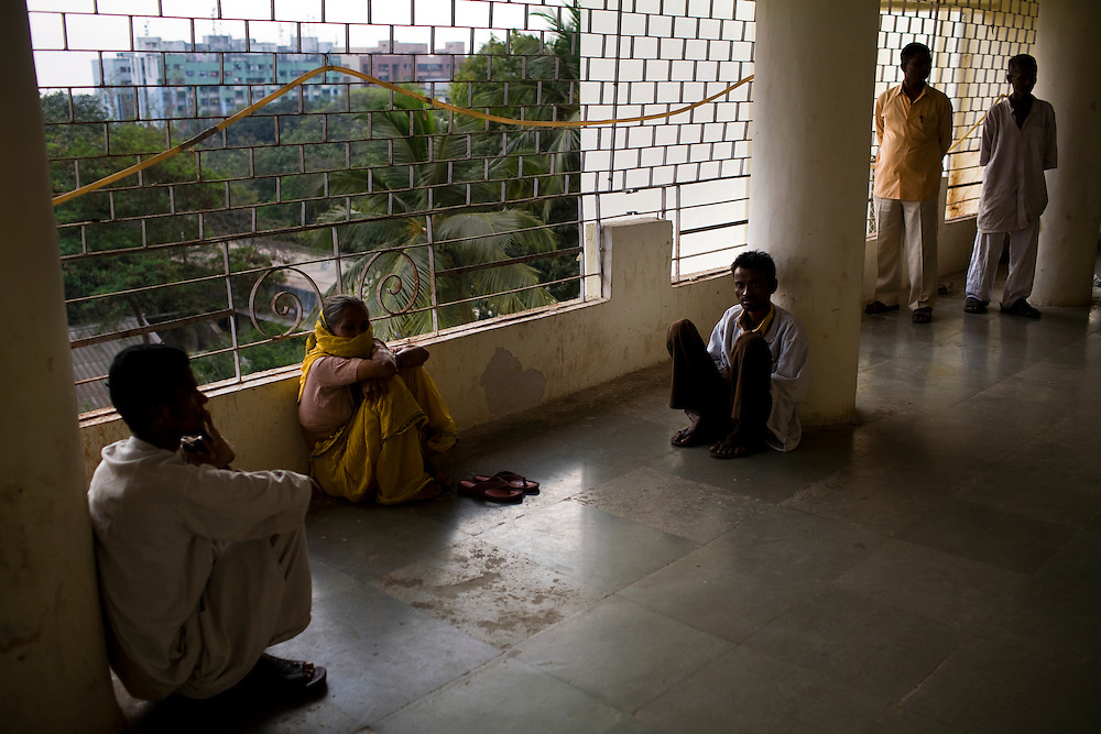 Family members wait in a hallway before visiting patients at the Group of TB Hospitals in Mumbai, India.