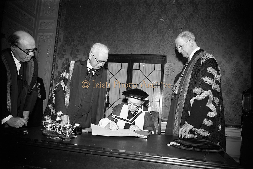 23/04/1964<br /> 04/23/1964<br /> 23 April 1964<br /> Honorary Degrees conferred at the National University of Ireland, Iveagh House, Dublin. <br /> Picture shows Mrs Cecil Woodham-Smith (Degree D.Litt.), Distinguished author and historian, signing the register after the ceremony watched by President Eamon de Valera (right), Chancellor of N.U.I.; Dr. Michael Tierney, President of U.C.D. and Dr. Seamus Wilmot, (left) Registar of the University.