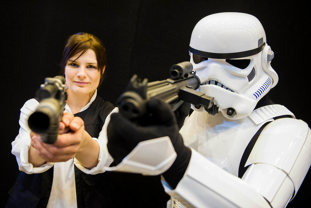 Janine Morton, 34, plays a gender adjusted Hans Solo with Seth Okai, 39, playing an Imperial Stormtrooper. Both are from Newcastle and part of a cosplay group that also works with charities, which allows them to build fully authentic costumes without treading on copyright problems. London Film and Comic Con 2014, (LFCC), at Earls Court, London, UK.