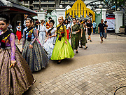 "08 APRIL 2017 - BANGKOK, THAILAND: Entertainers walk into the ""Amazing Songkran"" festival in Benchasiri Park in Bangkok. The festival was sponsored by the Tourism Authority of Thailand to highlight the cultural aspects of Songkran. Songkran is celebrated in Thailand as the traditional New Year's Day from 13 to 16 April. Songkran is in the hottest time of the year in Thailand, at the end of the dry season and provides an excuse for people to cool off in friendly water fights that take place throughout the country. Songkran has been a national holiday since 1940, when Thailand moved the first day of the year to January 1. Songkran 2017 is expected to be more subdued than Songkran usually is because Thais are still mourning the October 2016 death of revered King Bhumibol Adulyadej.       PHOTO BY JACK KURTZ"