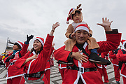 Participants  warm-up before taking part in the Tokyo Great Santa Run in Komazawa-daigaku Olympic Park, Tokyo, Japan. Sunday December 22nd 2019, The great Santa Run was first run in Tokyo in 2018. This years run saw over 3,000 people in Santa costumes run and walk a 4.3 kilometre course to raise money for medical charities in japan and water projects for the Maasai in Kenya.