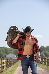 rugged masculine cowboy with open shirt carrying a saddle on a ranch
