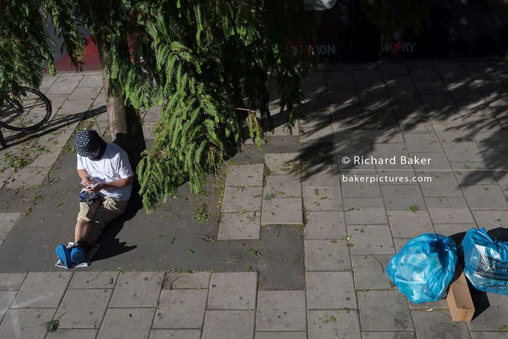 Aerial view of a man sitting at a bus stop near blue waste bags, on 21st September 2018, in London England