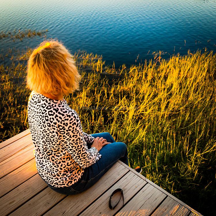 Golden light sunset falling on blond hair with blue water and lake grass, central Florida.