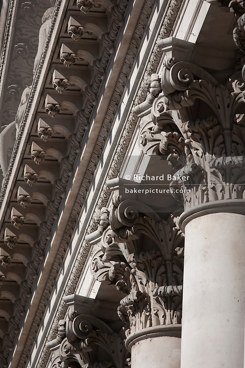 Corinthian columns and the top pediment of Royal Exchange in the City of London. The tall and solid Corinthian pillars of the 3rd Royal Exchange was built in 1842 by Sir William Tite.