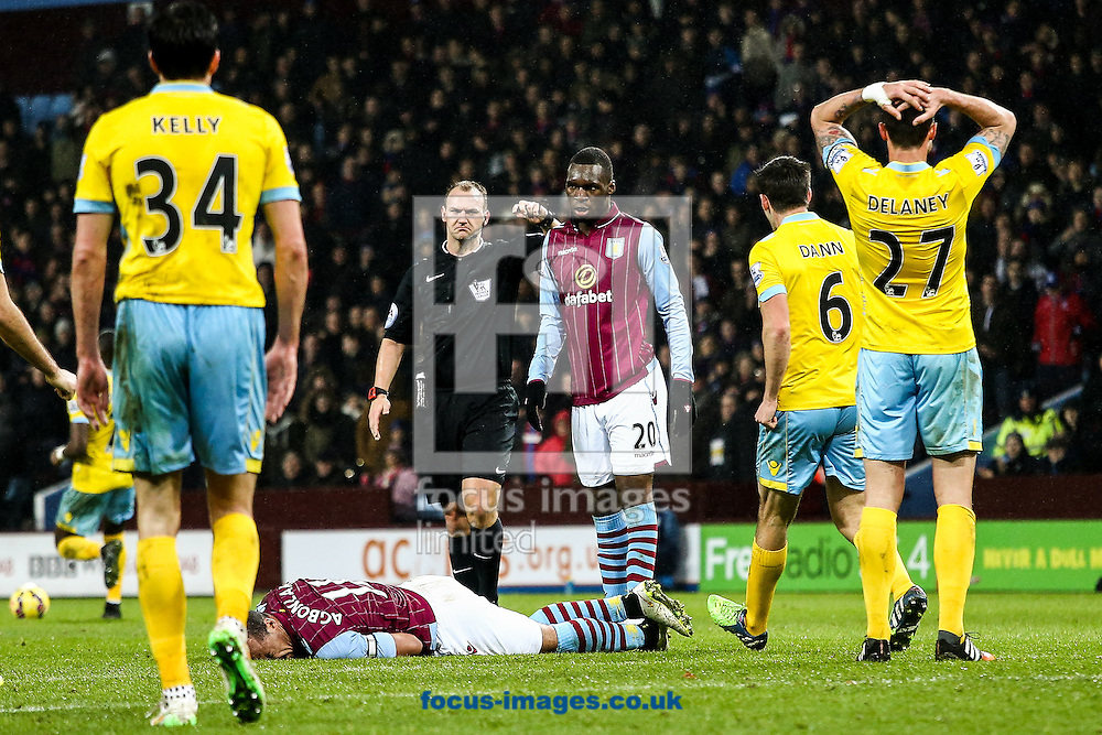 Gabriel Agbonlahor of Aston Villa lies injured after being fouled by Damien Delaney of Crystal Palace (right) during the Barclays Premier League match at Villa Park, Birmingham<br /> Picture by Andy Kearns/Focus Images Ltd 0781 864 4264<br /> 01/01/2015