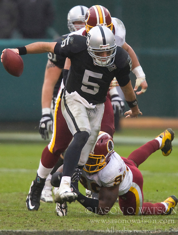 December 13, 2009; Oakland, CA, USA;  Oakland Raiders quarterback Bruce Gradkowski (5) avoids a tackle from Washington Redskins defensive end Andre Carter (99) during the second quarter at Oakland-Alameda County Coliseum.  Washington defeated Oakland 34-13.