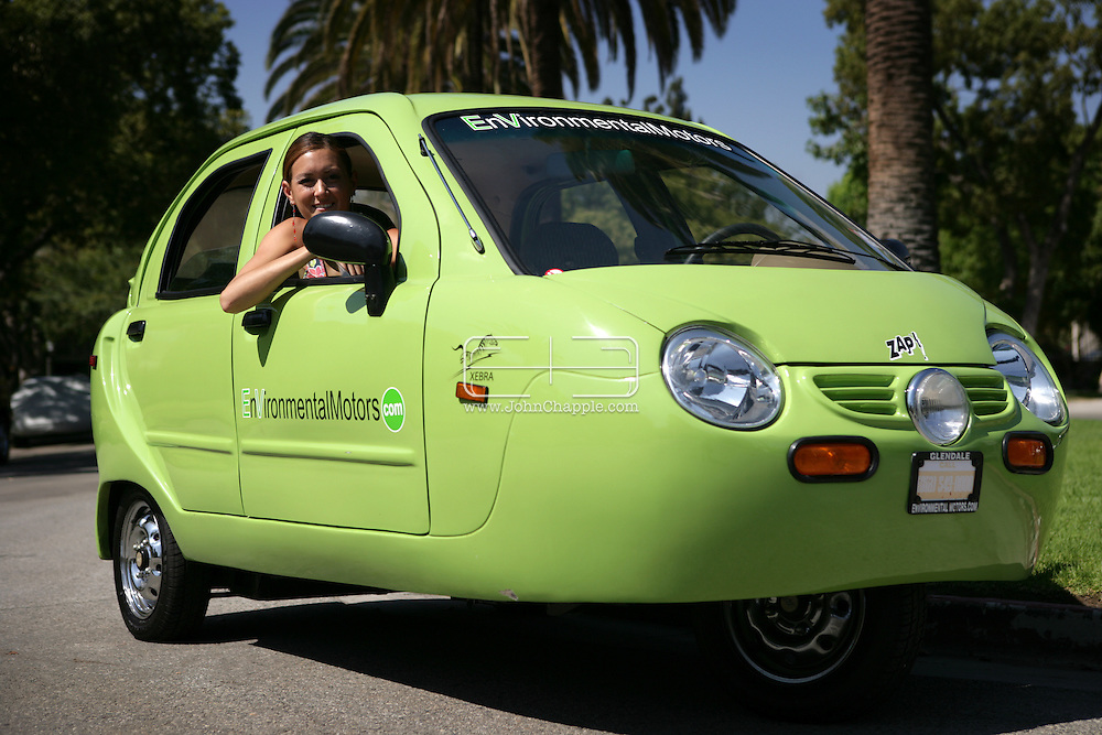 7th August 2007. Glendale, California. Del-Boy's car leaps into the next century. The classic three wheeler, made famous by British comedy, 'Only Fools And Horses', has seen a revival in the US. The new environmentally friendly Xebra three-wheeler, made by Zap! is 100% electric. The car which runs at speeds up to 40 mph has a range of 20-30miles on a single charge. With a price tag under US$10,000 (GB £4,950) it is even affordable as a second vehicle for Del-boy and Rodney's 'Trotters International Trading Company'. Pictured with the car is EnVironmental Motors director, Taryn M. Sokolow..PHOTO © JOHN CHAPPLE / REBEL IMAGES. .tel 310 570 9100.john@chapple.biz.www.chapple.biz.