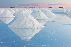 Conical mounds of salt reflected in the shallow water on the Salar de Uyuni, Bolivia,South America