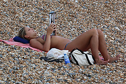© Licensed to London News Pictures. 24/06/2014. Brighton, UK. A woman sunbathing and relaxing on Brighton beach. Despite a cloudy day the weather is nice and warm with some people taking to the South Coast resort. Photo credit : Hugo Michiels/LNP