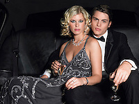 Couple in back of car drinking champagne eye contact