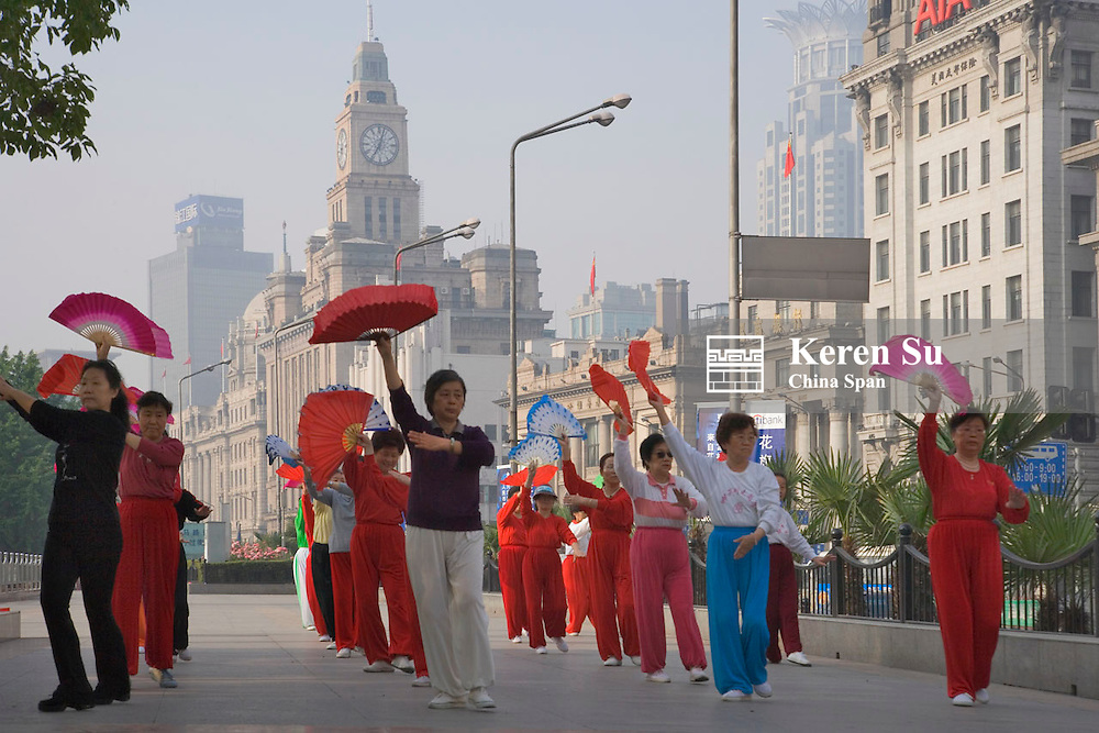People doing Taiji on the Bund, colonial buildings as background, Shanghai, China