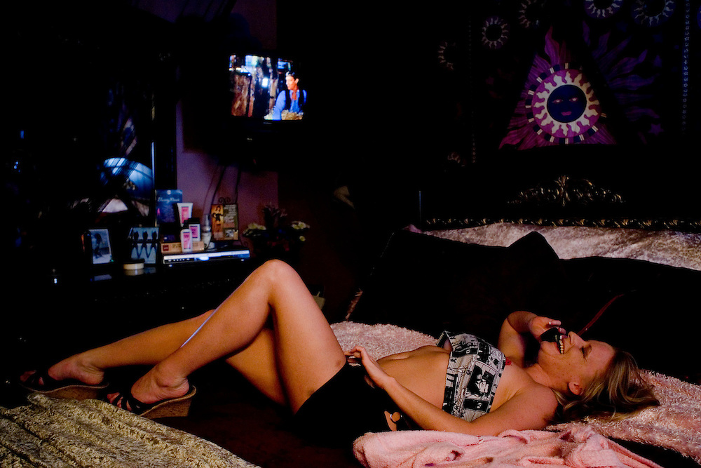 "Sex worker Lexi Lovelace takes a call on her bed at the Moonlite Bunny Ranch brothel in Mound House, NV on Saturday, July 28, 2006...The Moonlite Bunny Ranch brothel in Mound House, Nevada - just a few miles from the state capital in Carson City - first opened in 1955. The Ranch is a legal, licensed brothel owned by Dennis Hof. It's featured in the HBO series ""Cathouse."""
