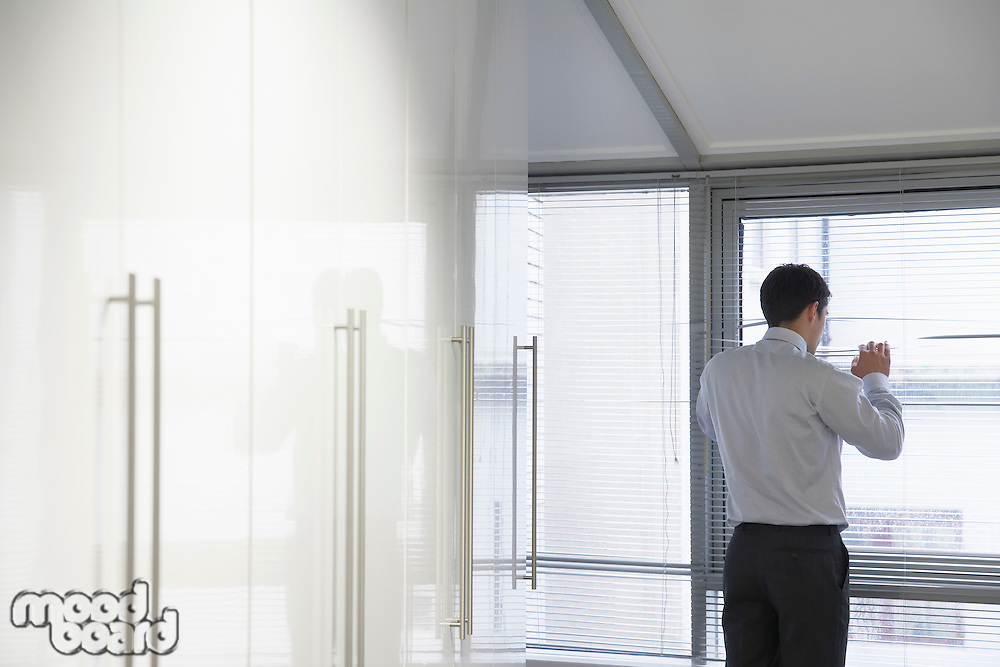 Businessman Looking out office Window through Venetian blinds
