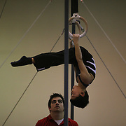 A young gymnasts is given advice by his coach during warm up for competition on the rings apparatus during the 21st American Invitational 2014 competition at the XL Centre. Hartford, Connecticut, USA. USA. 31st January 2014. Photo Tim Clayton