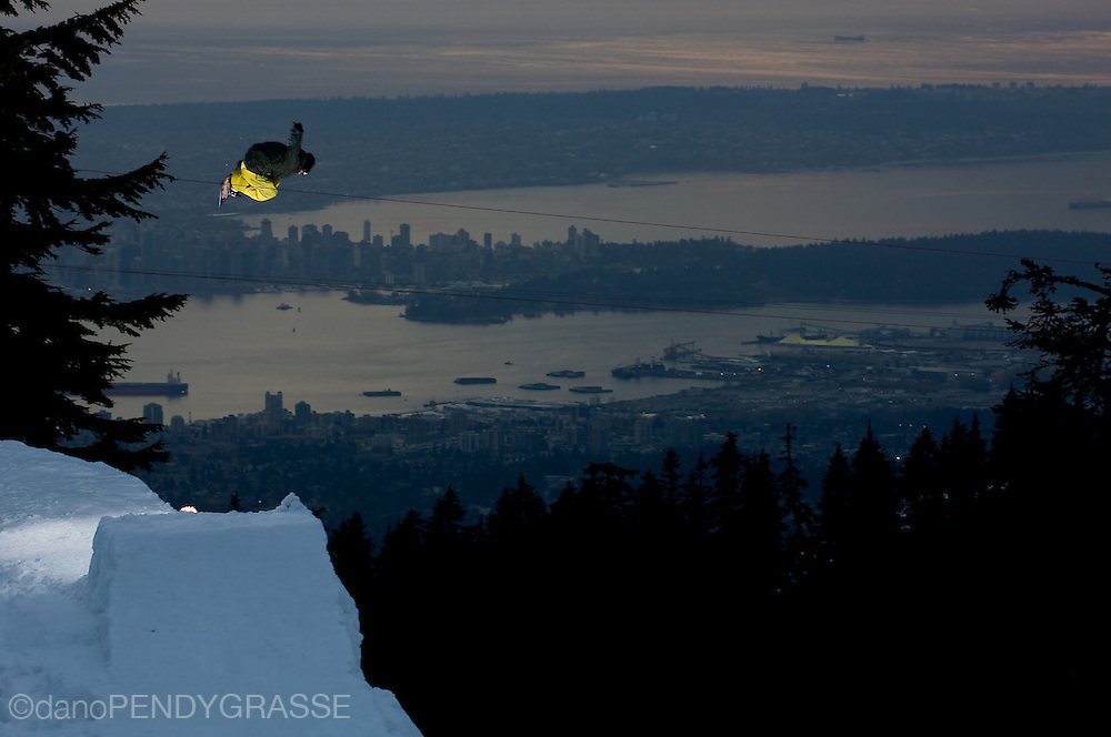 Professional snowboarder Mathieu Crepel flies over Vancouver, BC at dusk.