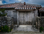 """A solid, storm proof traditional house on the Okinawan island of Taketomi, with its """"aka-gawara"""" red terracotta roof tiles held down by white mortar to bond the edges preventing them from being blown away during typhoons.  A wall made from coral protects the house from storm winds but typhoons are forecast to become stronger as climate change raises sea temperatures which fuel the storms.  Storm surges will also grow larger further threatening residents and damaging ports in this island nation.  Okinawa, Japan"""