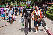 20 MAY 2010 - BANGKOK, THAILAND: A Thai police officer helps a woman with an injured foot to a waiting bus at Thai police headquarters in the Ratchaprasong Intersection in Bangkok Thursday. The woman was one of thousands of people who took shelter in Wat Pathumwanaram during heavy fighting between anti government protesters and the army on Wednesday. The day after a military crackdown killed at least six people, Thai authorities continued mopping up operations around the site of the Red Shirt rally stage and battle fires set by Red Shirt supporters in the luxury malls around the intersection. PHOTO BY JACK KURTZ