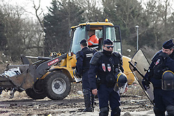© Licensed to London News Pictures. 02/03/2016. Calais, France. French police stand next to digging equipment being used to clear part of the migrant camp knows as 'The Jungle' in Calais, France. Violence has broken out in parts of the eviction zone where inhabitants have resisted efforts to move them. Photo credit: Rob Pinney/LNP