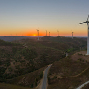Aerial panoramic Wind farm turbines silhouette at sunset. Clean renewable energy power generating windmills. Algarve countryside. Portugal.
