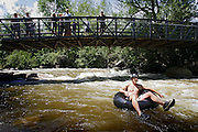 C.J. Fox (right), 21, of Lakewood passes by a bridge crowded with onlookers after dropping over a small waterfall on Boulder Creek Monday July 10, 2006 while tubing a section of the creek near Eben G. Fine Park in Boulder, Co. Fox said he has tubed the creek before this year but when it was much lower. Recent rainfall has significantly raised water levels on local creeks and rivers including Boulder Creek in Boulder. The rainfall has added to water levels enough to make Boulder Creek a fun place to play in on a tube but also has made it a potentially dangerous place with fast moving water and numerous branches in the water..(MARC PISCOTTY/ © 2006)