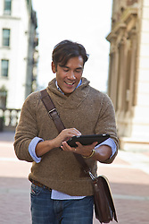 Asian American college student using an ipad