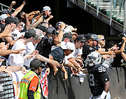 Sep 30, 2018; Oakland, CA, USA;  Oakland defensive tackle Frostee Rucker (98) celebrates with fans after cornerback Gareon Conley (not pictured) scores on a 36 yard interception return in the first quarter of a game between the Oakland Raiders and the Cleveland Browns. The Raiders defeated the Browns 45-42 in overtime. Mandatory Credit: Spencer Allen-Image of Sport