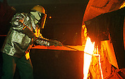 29 JANUARY 1999  - EL PASO, TEXAS: Manny Barrios, a refiner at the Asarco copper smelter in El Paso, Texas, skims molten copper coming out of the furnace at the smelter. Asarco mothballed the smelter for at least three years because of low prices in the copper industry. In mid 1997, copper was selling for approximately $1.20 per pound, it is currently selling for about .65 cents per pound, forcing copper producers like Asarco to take drastic belt tightening measures. About 370 workers were laid off as the plant's machinery was mothballed. Closure of the Asarco smelter comes on the heels of the closure of copper mines in southern New Mexico owned by the Phelps-Dodge company, an Asarco competitor. Asarco officials have said they may reopen the plant if copper prices rebound. Photo by Jack Kurtz / ZUMA Press