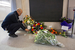 © licensed to London News Pictures. London, UK 18/11/2012. A Tube staff putting flowers together which were left to remember 31 people who died at the fire incident at King's Cross Underground station 25 years ago. Photo credit: Tolga Akmen/LNP
