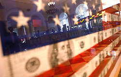 A visitor is reflected in a picture of the American flag made out of US currencies in the Museum of American Finance in New York, New York, USA, 22 October 2008. As Wall Street descend into a financial turmoil not seen since the stock market crash of 1929 and financial businesses were pommeled into rampant sell-offs in stocks and face regulatory changes to their business practices, professionals and non-professionals working in the district's banks, stock-trading houses and insurance companies are showing stress and a gloom not unlike the times of the Great Depression.