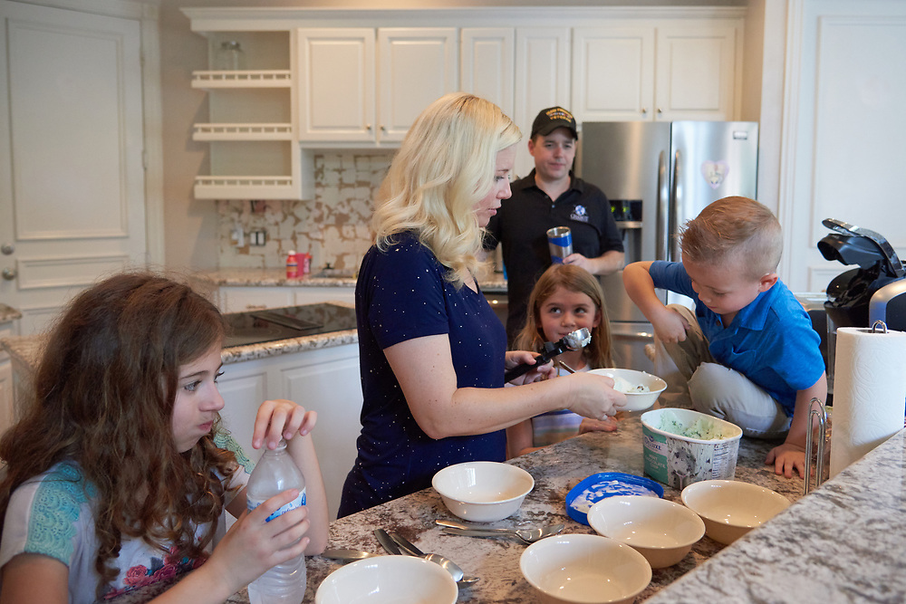 Paul and Brenda Chabot scoop ice cream for their four children at their new home in McKinney, Texas on August 13, 2017. (Cooper Neill for The New York Times)