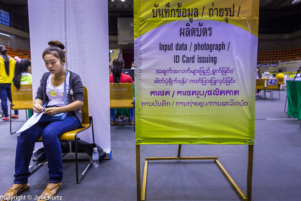 "17 JULY 2014 - BANGKOK, THAILAND:  An undocumented Cambodian woman waits her turn at the temporary ""one stop service center"" in the Bangkok Youth Center in central Bangkok. Thai immigration officials have opened several temporary ""one stop service centers"" in Bangkok to register undocumented immigrants and issue them temporary ID cards and work permits. The temporary centers will be open until August 14.   PHOTO BY JACK KURTZ"