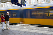 In Baarn doet een vrouw haar oren dicht als de intercity voorbij het perron raast.<br /> <br /> In Baarn a woman is putting her fingers in her ears as a intercity is passing the platform at high speed.