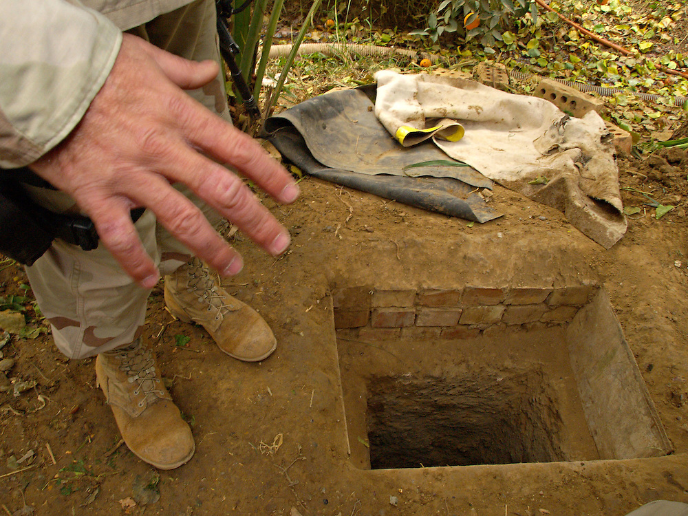 Dec15th 2003.ad Dawr, Iraq..Saddams hideout..A US soldier examines the entrance to a small underground chamber in which Saddan was dicovered and captured at a small farm near Tilkrit...15th December 2003