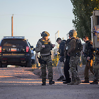Members of an FBI tactical team and McKinley County Sheriff's officers gather in the intersection of Ironwood Street and Rosita Avenue for a drug raid at a home in Gamerco Tuesday.