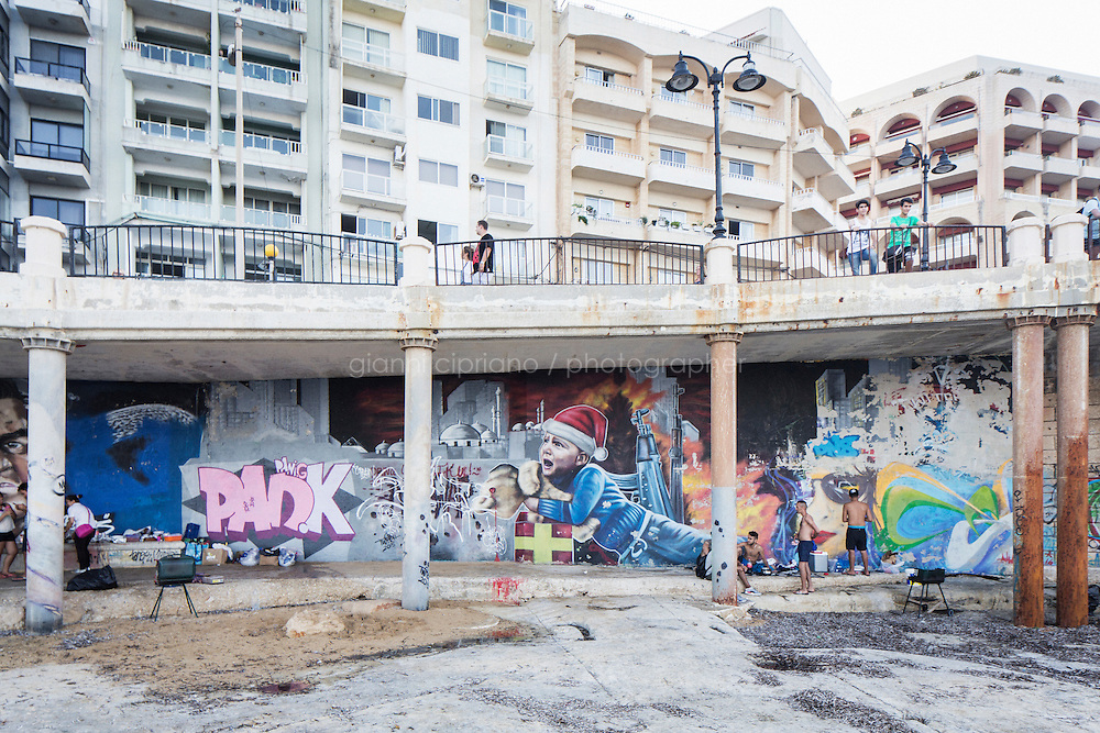 SLIEMA, MALTA - 28 AUGUST 2016: The &ldquo;No War&rdquo; graffiti by street artist &ldquo;Twitch&rdquo; (James Grimaud), depicting a crying child carrying a teddy bear that&rsquo;s been shot in the head, is seen here under a overhanging footpath along the coast in Sliema, Malta, on August 28th 2016.<br /> <br /> While many cities across the world denounce the defacing of a public property, on the Mediterranean island of Malta it is encouraged.<br /> <br /> According to Sandra Borg of Arts Council Malta, street art projects &ldquo;engage with numerous communities and contribute directly to urban regeneration&rdquo;. Funding from Arts Council Malta, allows schools to offer additional creative arts subjects and many choose street art; with &lsquo;NO WAR&rsquo; creator, James Grimaud, teaching students sketching, stencil making and aerosol use.