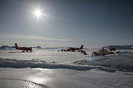 Canadian Rangers patrol set up camp on icepack next to an iceberg on Devon Island, Nunavut, during Nunalivut 2012 sovereignty exercise by Canadian Forces in arctic Canada. Ski-equipedTwin Otters land next to the camp to resuply the patrol with snowmobile and heating fuels. 18 April 2012.