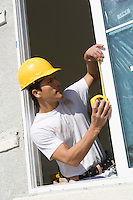Construction Worker measuring window frame