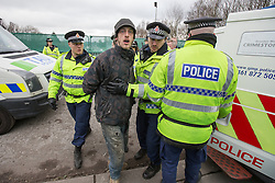 © Licensed to London News Pictures . 17/03/2014 . Barton Moss , Salford , UK . A man is detained by police as protesters attempt to block lorries from accessing the iGas site . Happy Mondays dancer , Bez ( Mark Berry ) , joins protesters at the Barton Moss anti-fracking protest site in Salford today (Monday 17th March 2014) . Bez has said he will stand for MP in the constituency of Salford and Eccles in 2015 . Photo credit : Joel Goodman/LNP