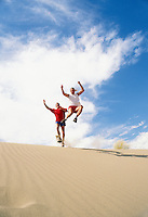 Two late 20's Caucasian men leaping off a sand dune.  Near Vantage, Washington, USA.  Frenchmans Coulee.<br />