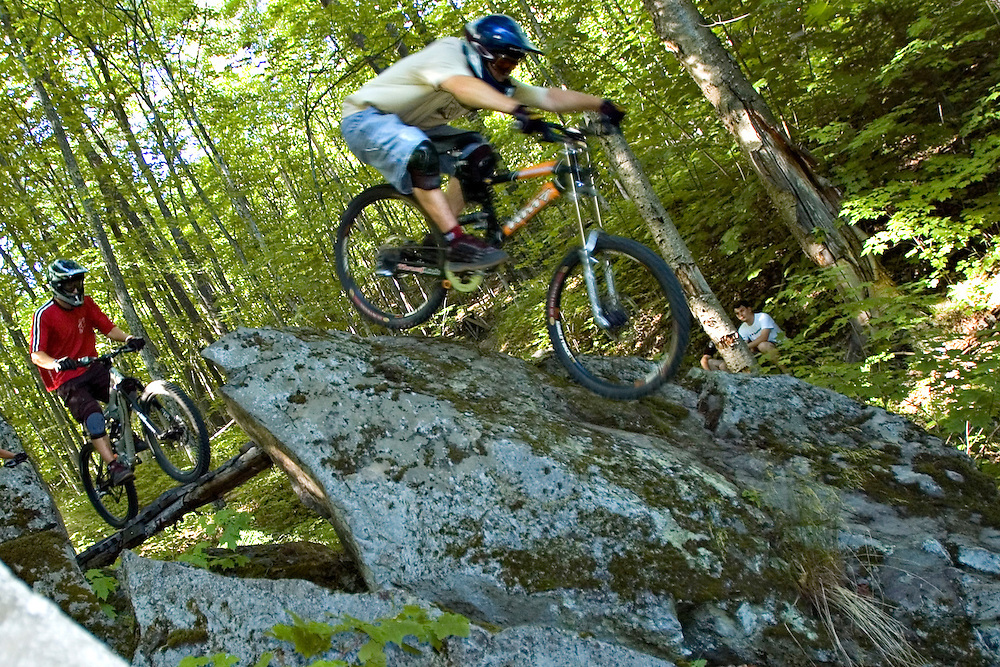 Mountain bikers ride the steep face of a large rock while freeriding near Marquette Michigan.