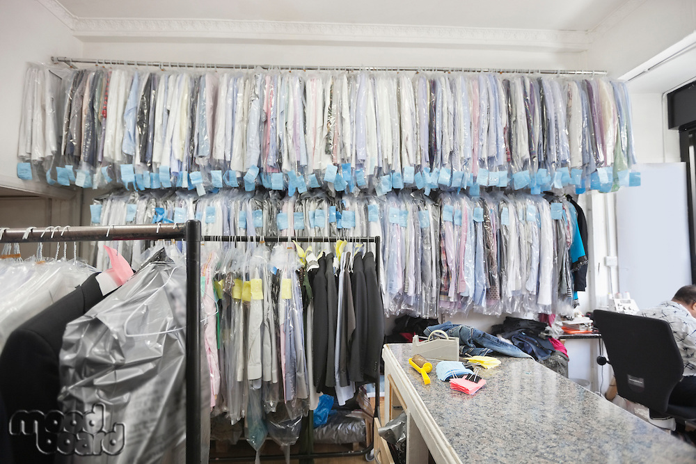 Dry cleaned shirts hanging on clothes rack while tailor working in corner of the room