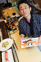 Portrait of a happy chef with Japanese sushi in restaurant