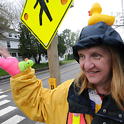 "Lisa Green, crossing guard at the corner of Longfellow and Maine streets in Brunswick, has a wave or a smile for nearly every passerby. Her habit of wearing funny hats began last year when serving near Jordan Acres School.   ""I was clipped,"" she said, ""and it hurt!""  The guy {who hit me} kept saying that he didn't see me -- so I decided to start making it impossible to not see me."" She added, "" My best hats come out at Halloween!""  Photo by Roger S. Duncan."