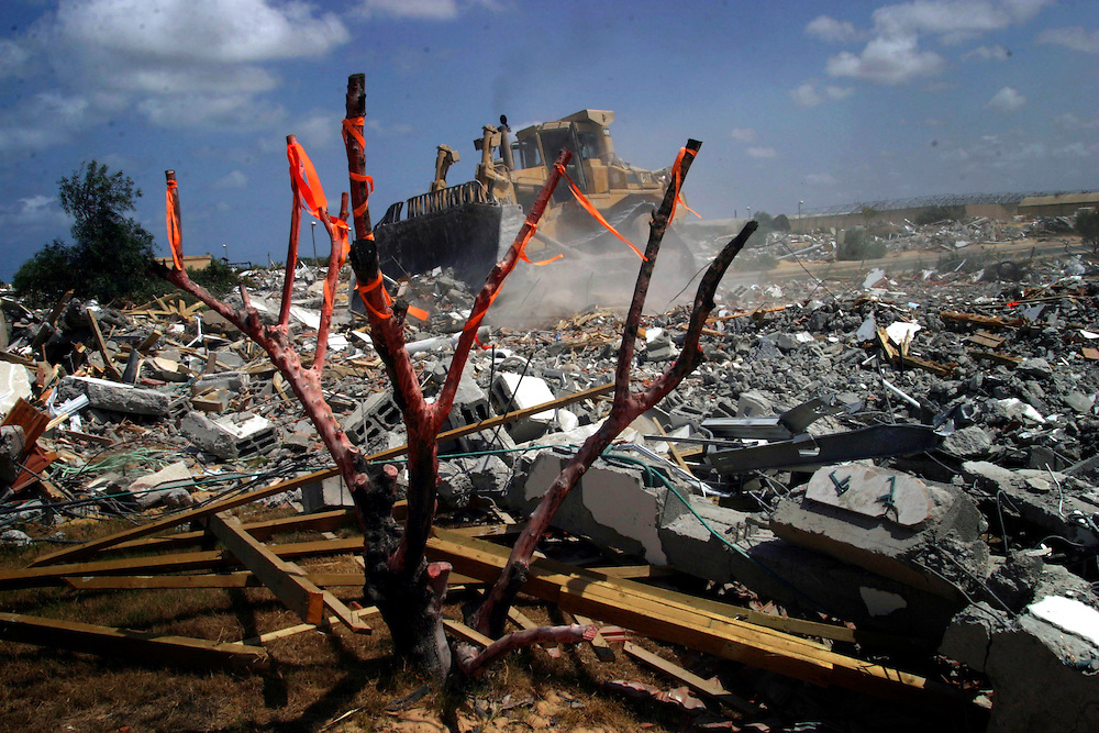 An Israeli bulldozer demolishes a house in the Jewish settlement of Gadid,Gaza Strip, August 25, 2005.