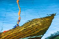 Spegling i vatten av segelbåt i trä i Stockholms skärgård. / Reflection in water of the wooden sailboat in the Stockholm archipelago.